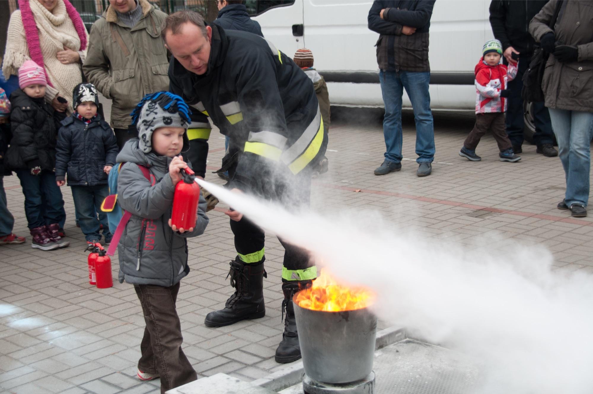 Małe dziecko gasi pożar małą gaśnicą